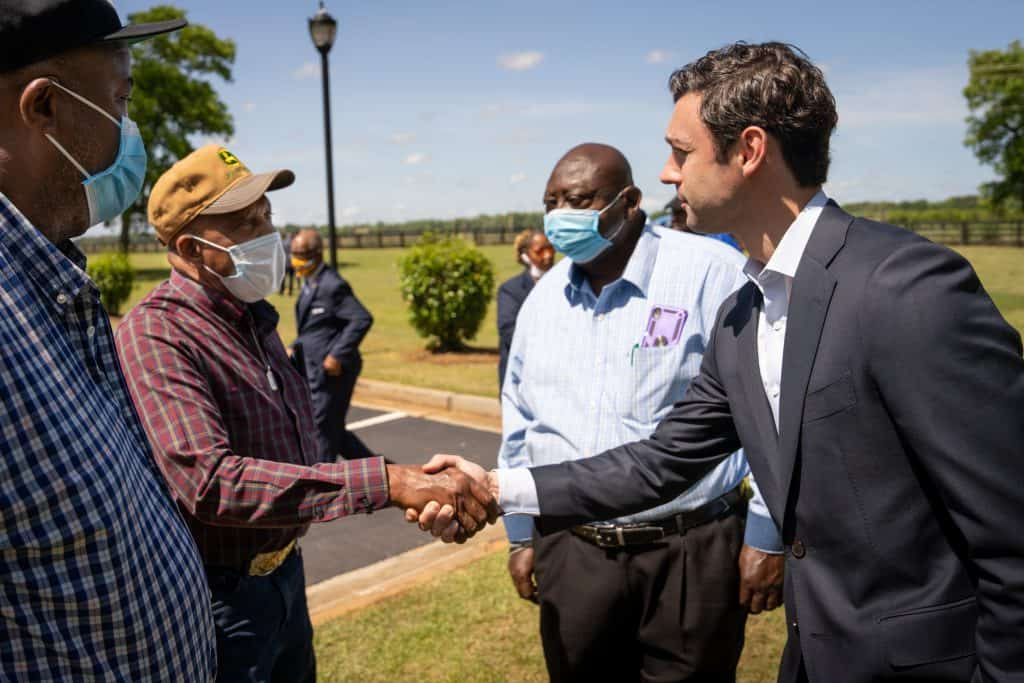 Senator Ossoff shaking hands with a farmer while two others look on outside in Fort Valley, Georgia.